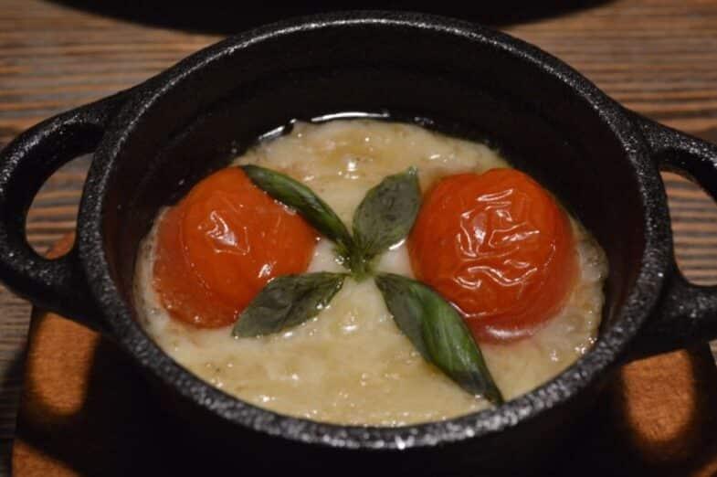 Provolone a la brasa con tomate asado y albahaca fresca.