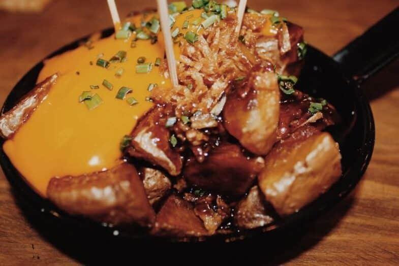 """""""Las Tony"""", patatas con cebolla crujiente, queso cheddar y su salsa BBQ."""