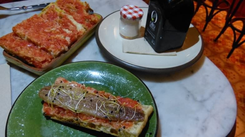 Sardina ahumada y tapa de pan con tomate, junto a la sal Maldon y el aceite de oliva.