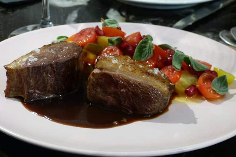 Magret de pato con ensalada de tomate, granada y orégano fresco.