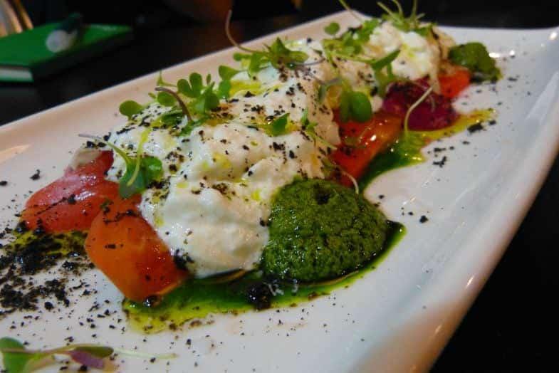 Queso Stracciatella de Puglia con tomate de temporada, hinojo, pesto de albahaca y remolacha.